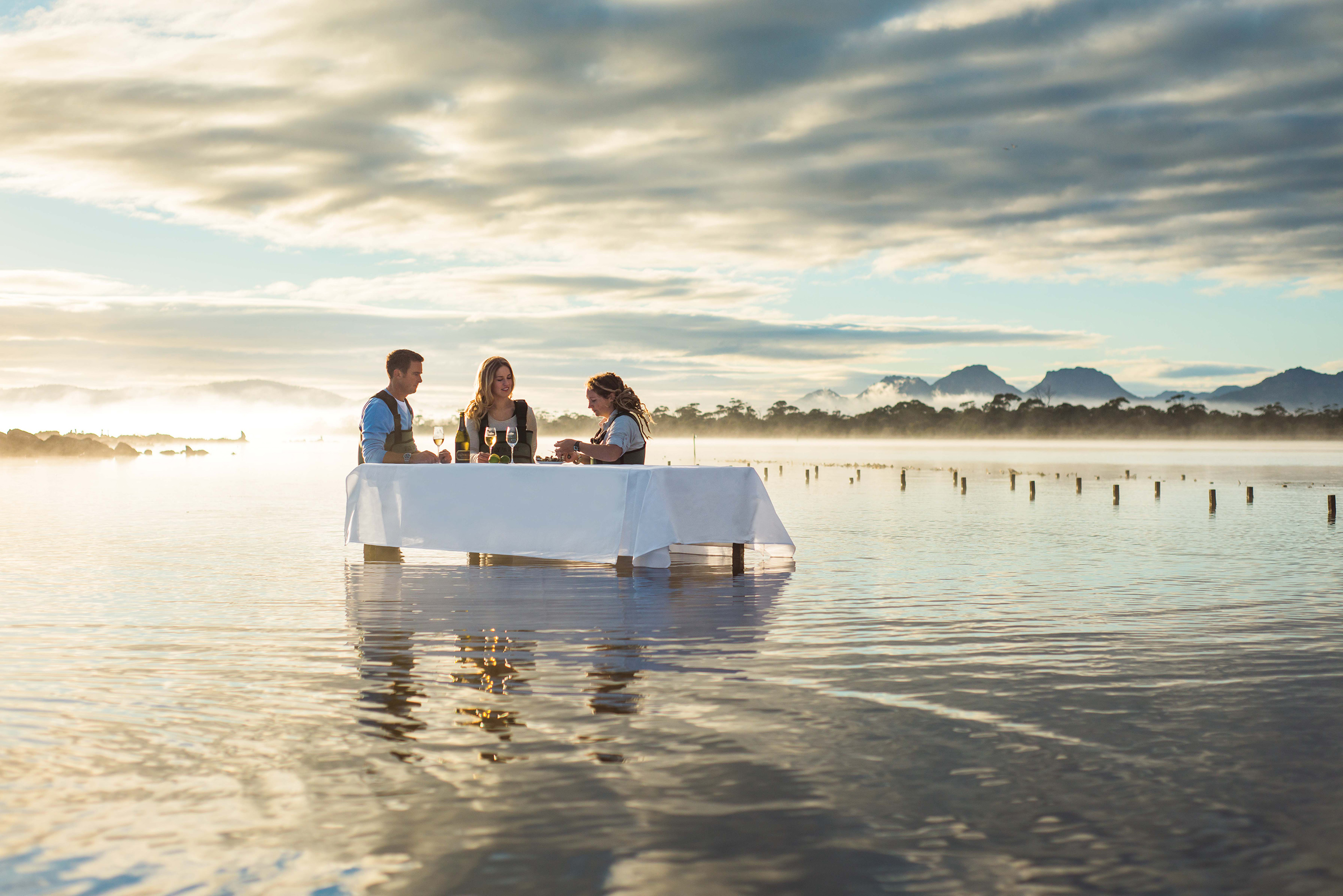 three people eating oysters at table in the ocean