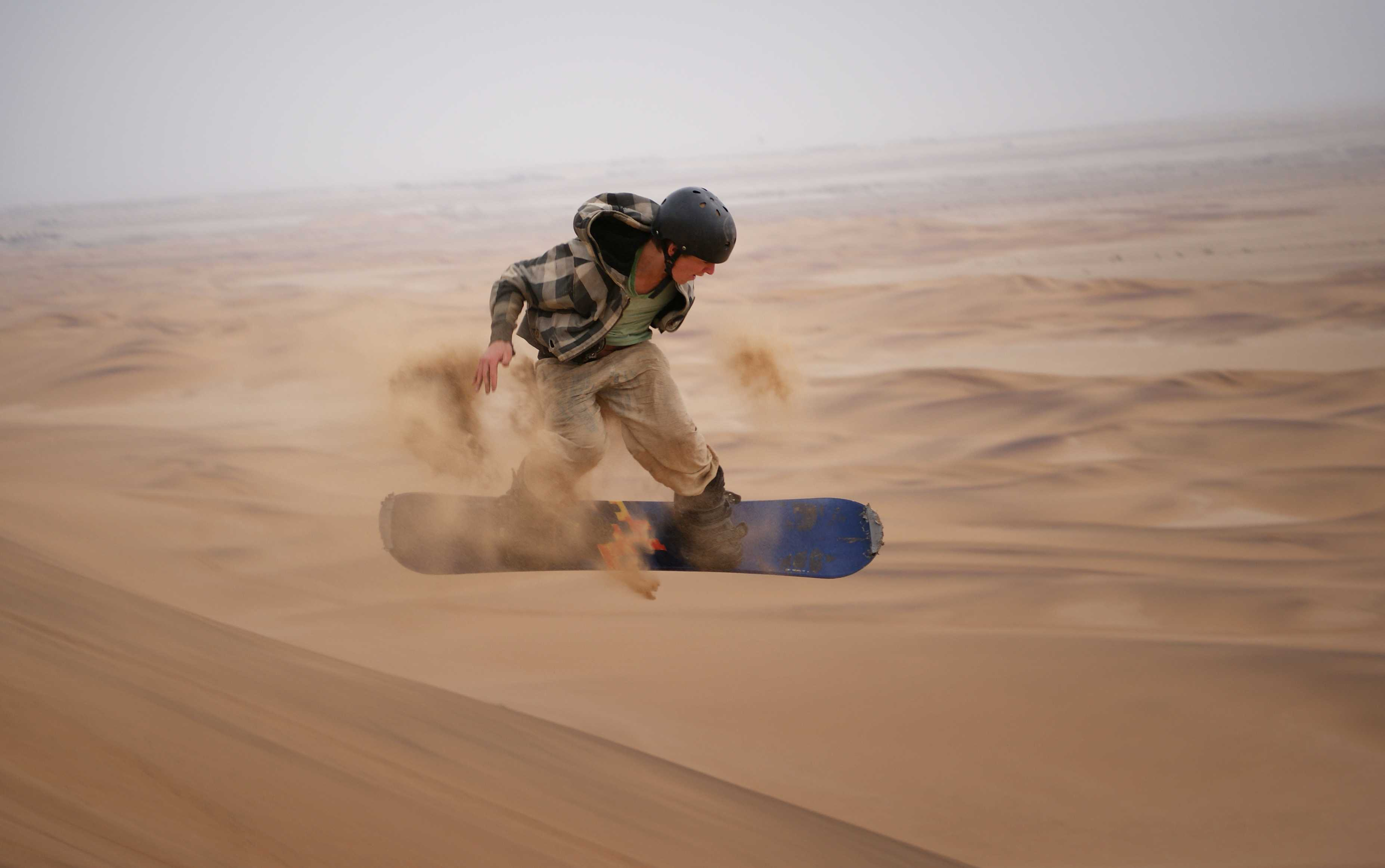 guy sandboarding in namib desert