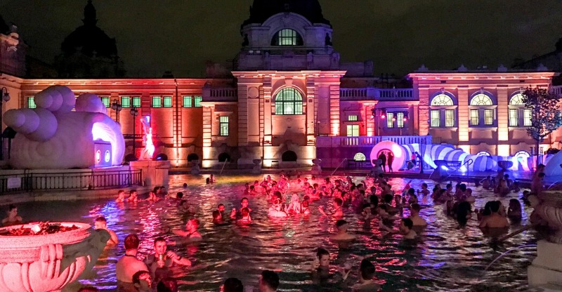 lit up buildings and crowds in pool at sparty budapest