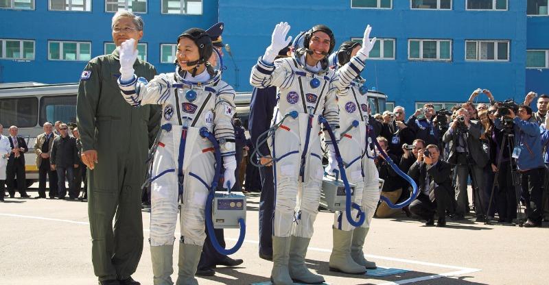 astronauts waving at rocket launch
