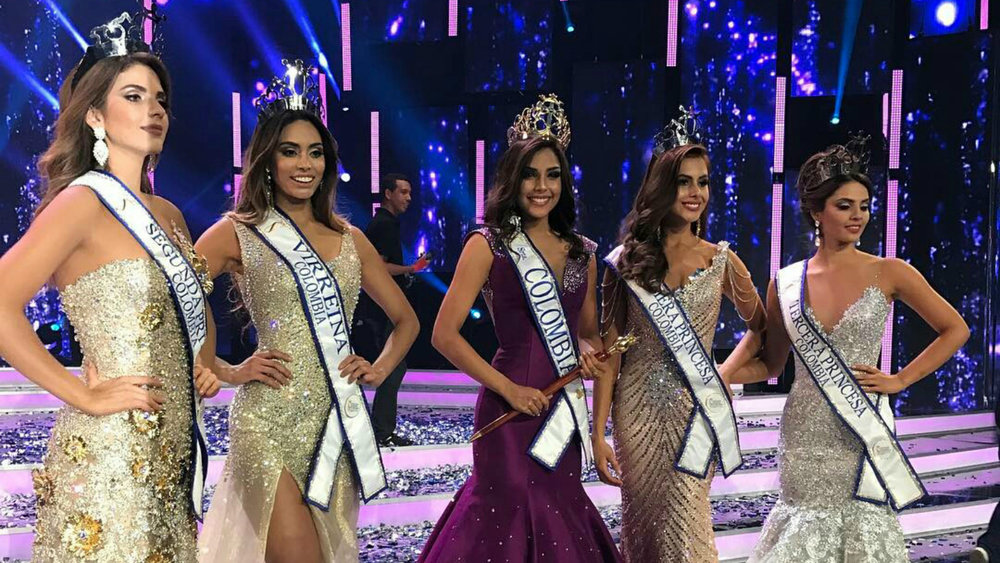 miss colombia contestants posing on stage in gowns