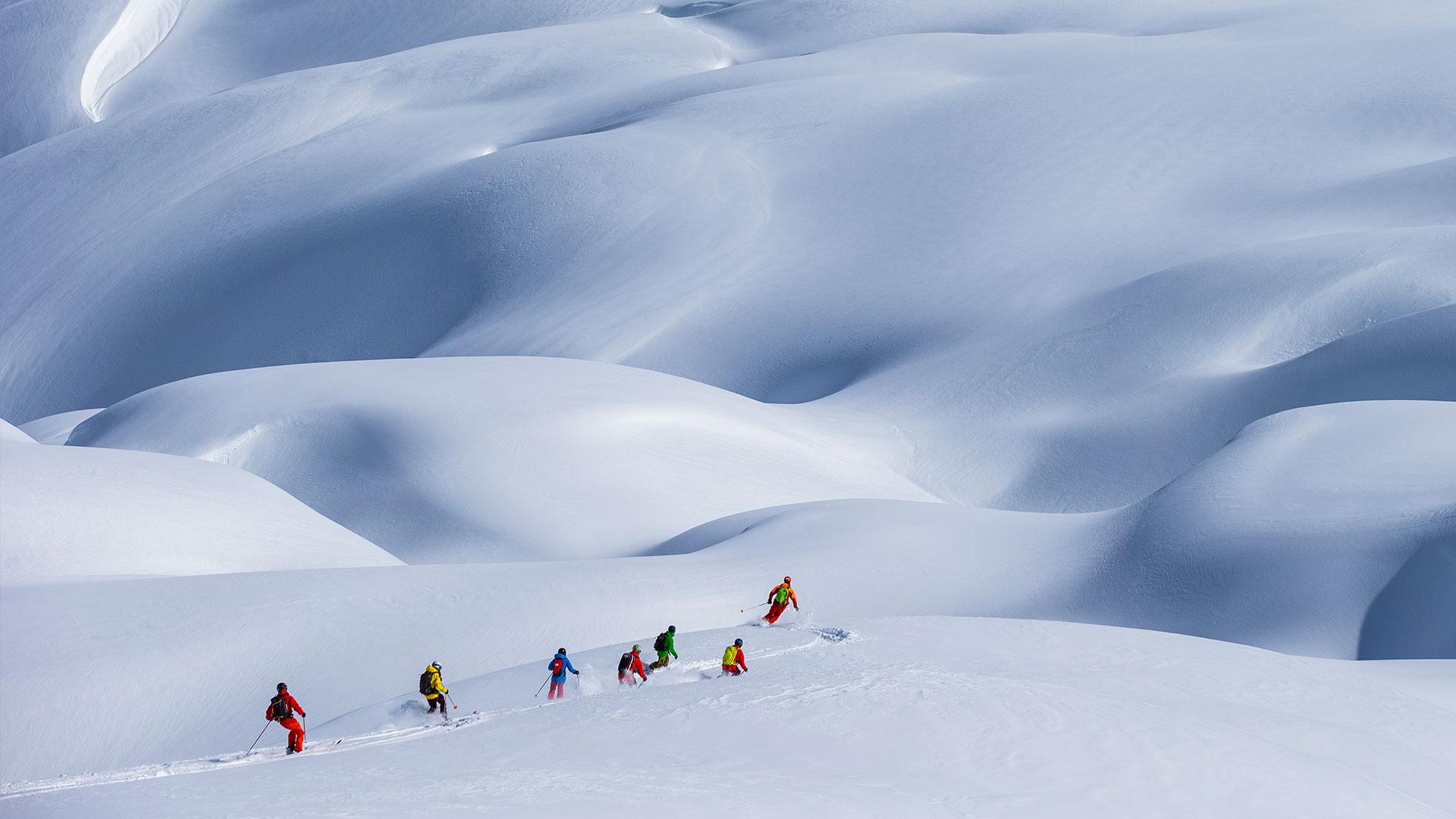 heli-skiing group skiing down mountain in Canada