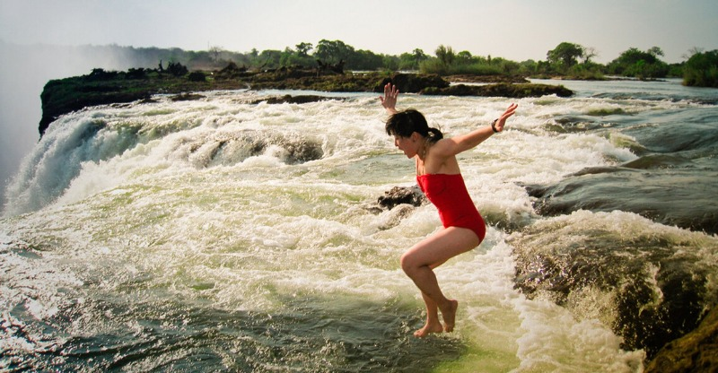 woman jumping into devil's pool, victoria falls with rainbow