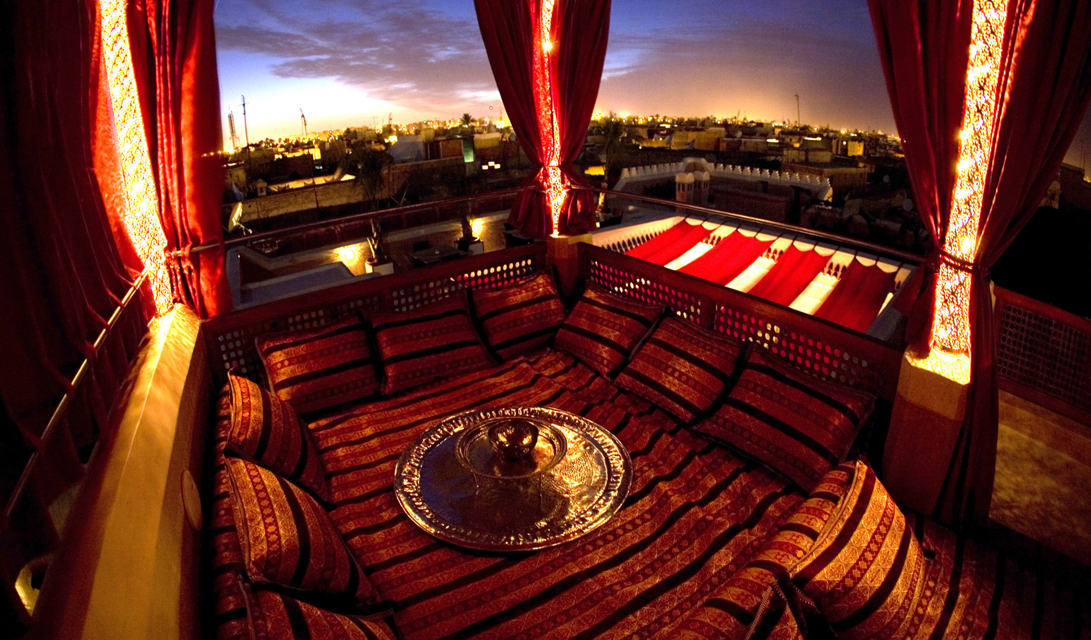 AnaYela rooftop terrace with deep red cushions and gold detail