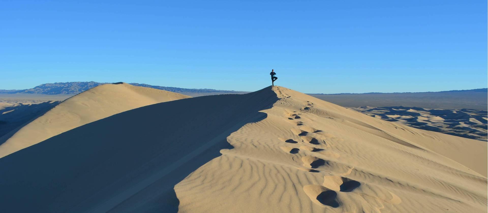 person doing yoga on desert ridge on gobi desert trek