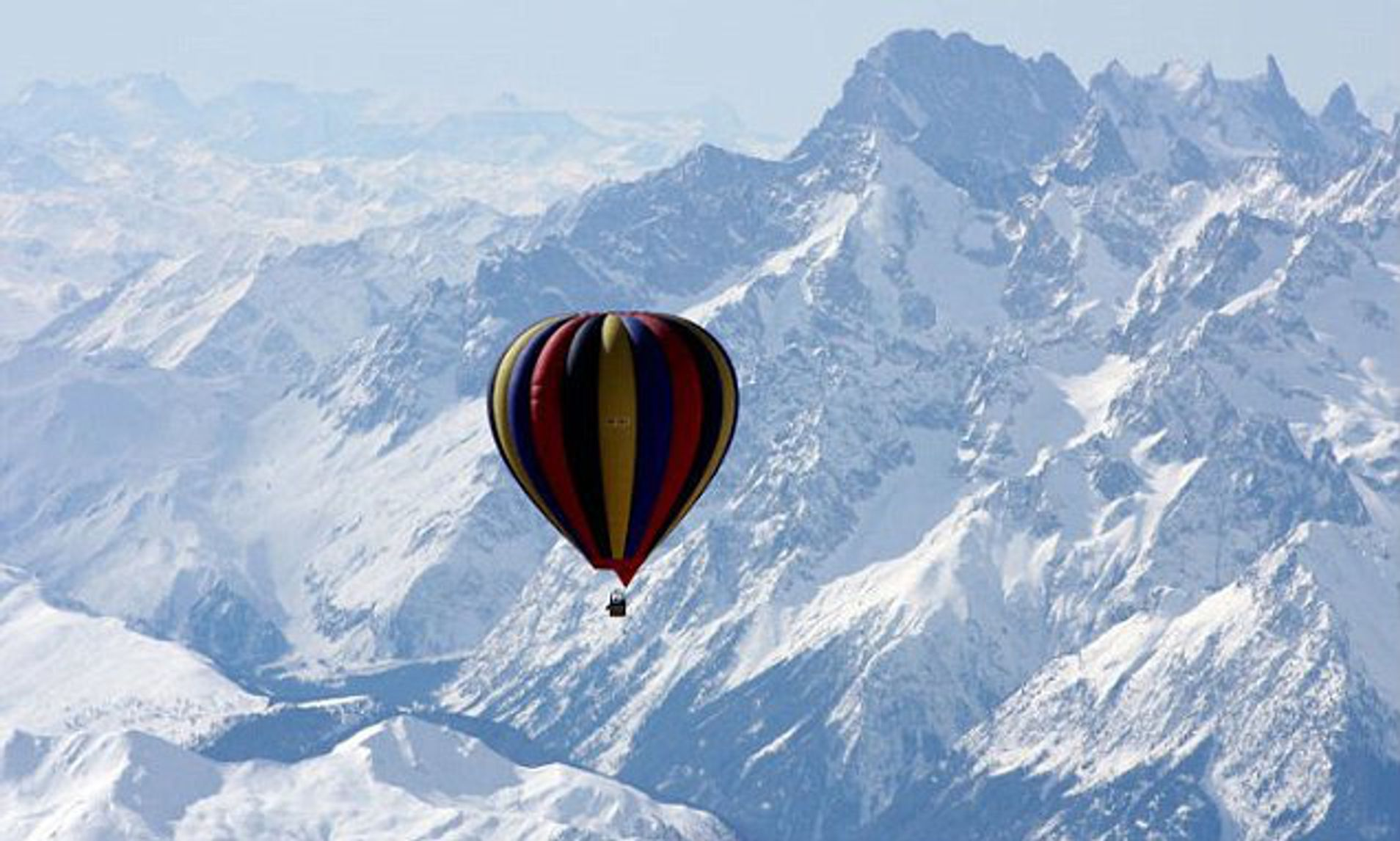 Hot Air Balloon soaring over snowy mountains of Everest range