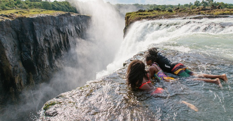 people looking over edge in Devil's pool, Victoria Falls