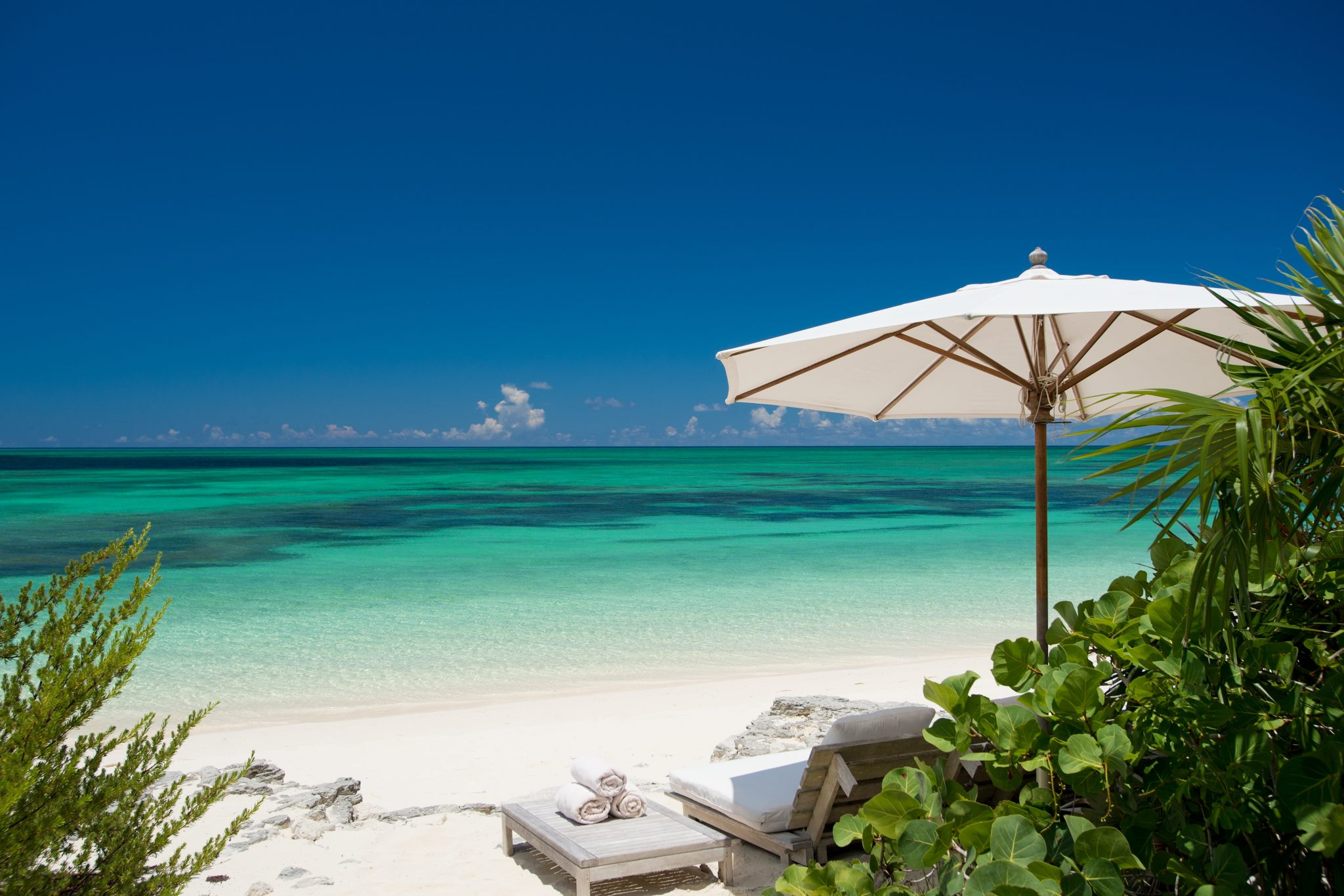lounger and umbrella on beach at Turks and Caicos retreat