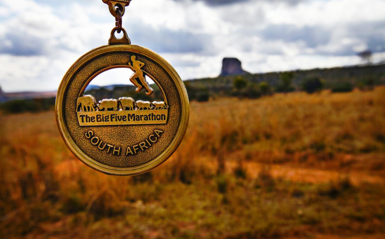 big 5 marathon medal in front of african savannah