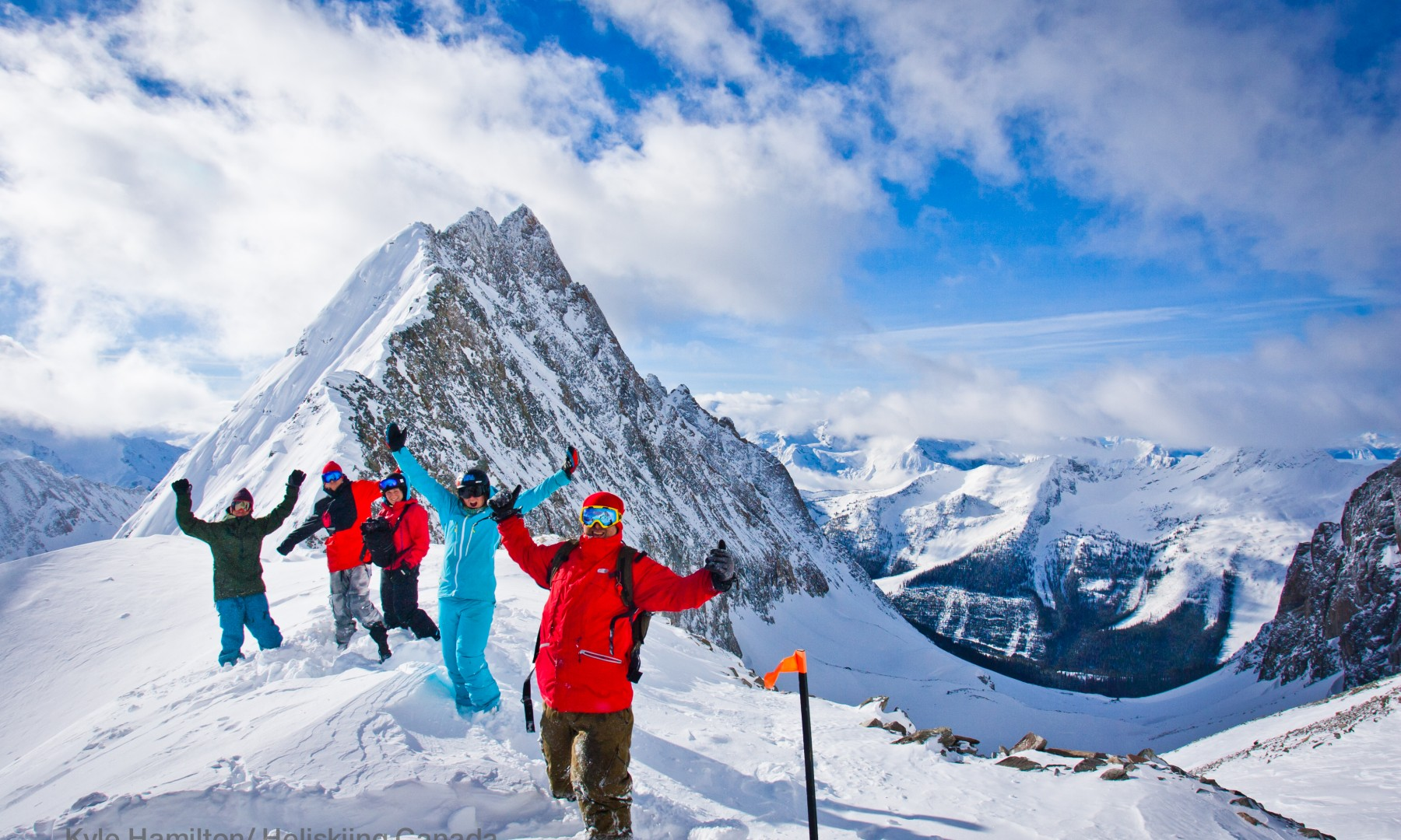 heli-skiing group waving on top of mountain in canada