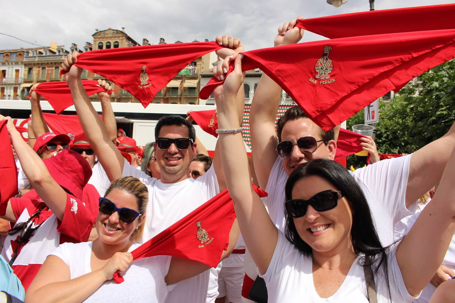people celebrating running of the bulls with red neckerchiefs