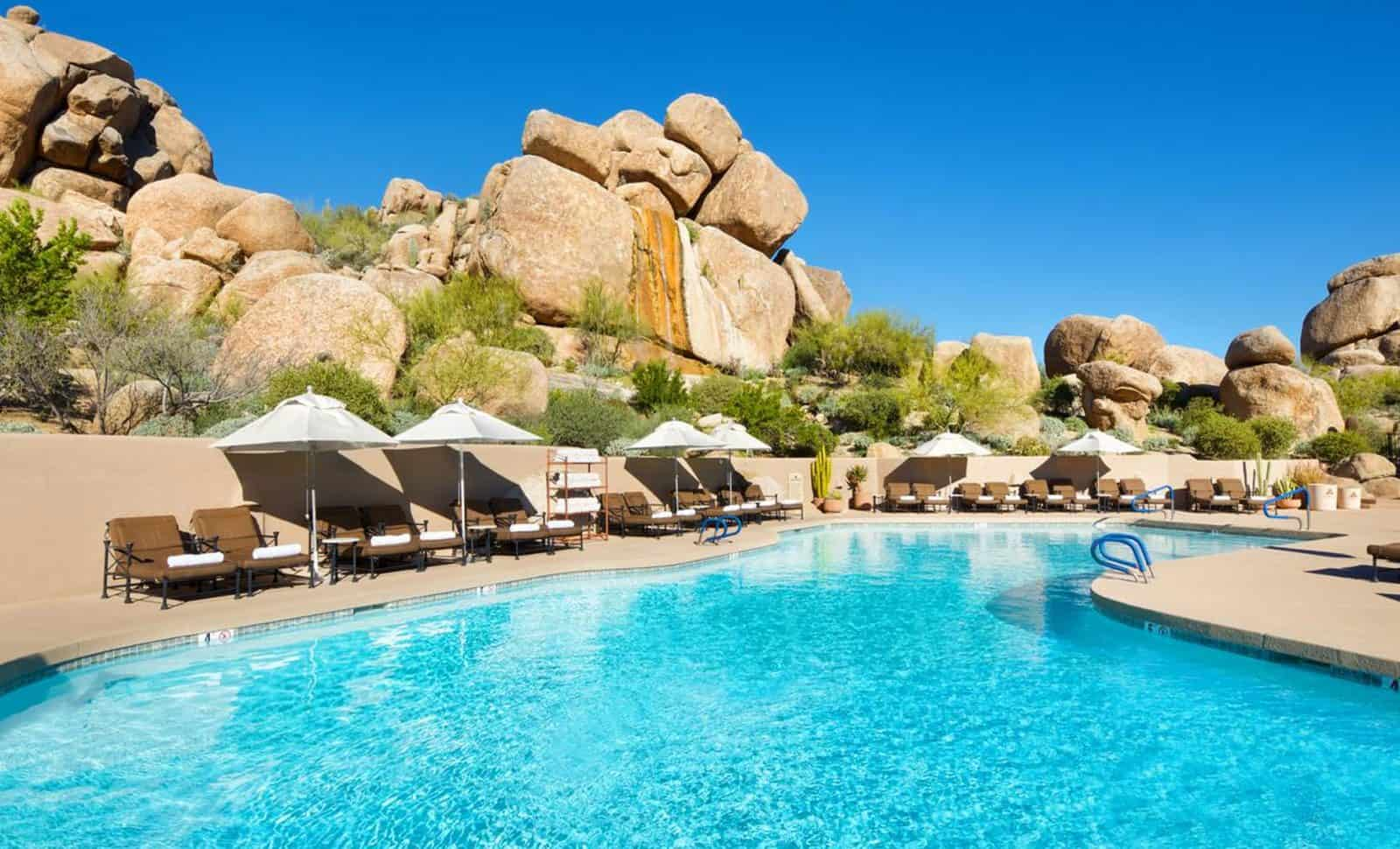 Boulders resort swimming pool and loungers next to rock face