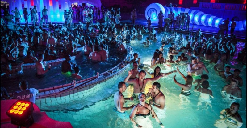 people partying in pool at night at Sparty Budapest