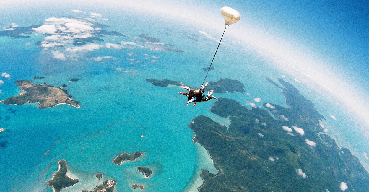 two people parachute skydiving over great barrier reef
