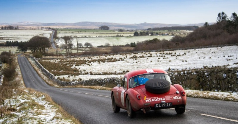 le jog classic car driving in snowy countryside