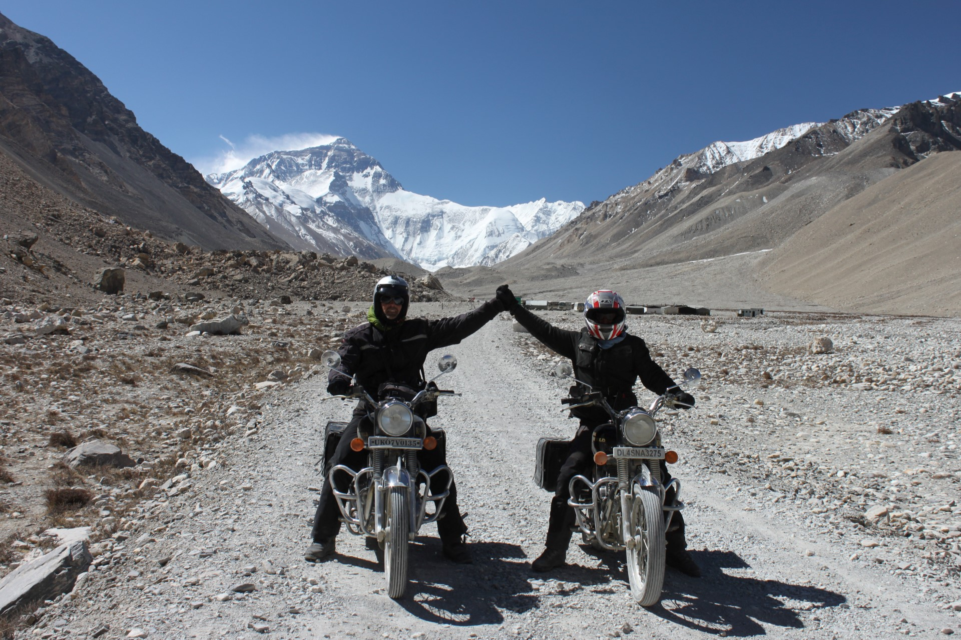 two bikers the arms up in mountains on Indian Motorbike Tour