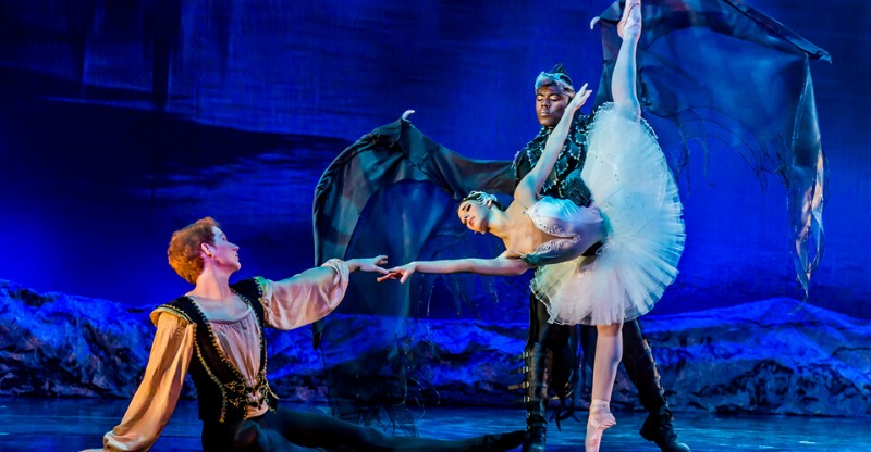 three swan lake ballerinas on stage