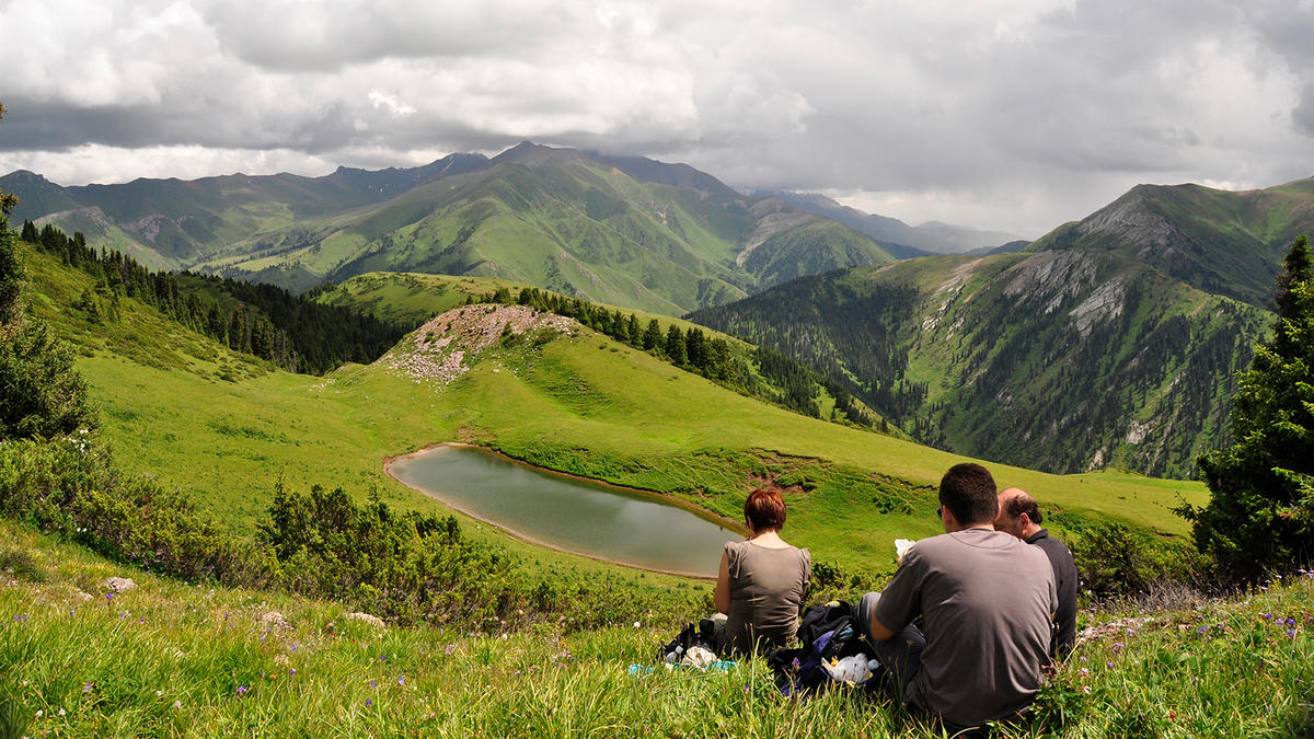 hikers sitting looking at view of mountains on silk tour kazakhstan