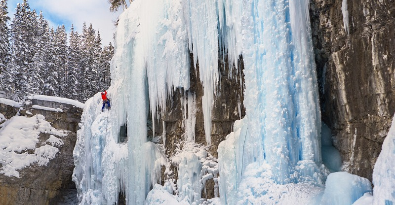 A climber midway up a stunning ice waterfall