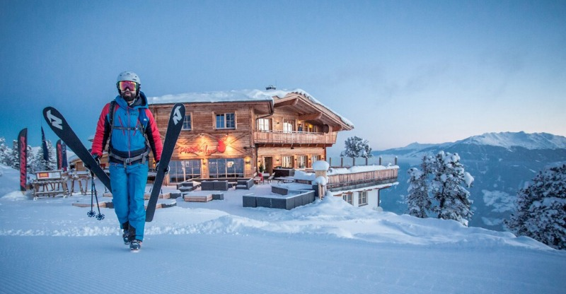 Skier with a wooden winter chalet overlooking the mountains