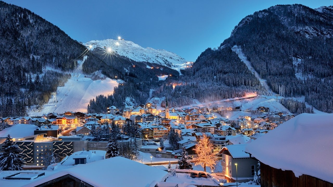 Beautiful town lit up at night in the snowy mountains of Austria