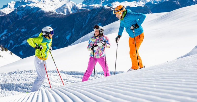 Three skiers on the pistes of the Dolomite Mountains