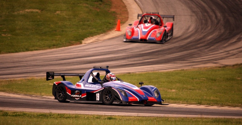 Two cars racing on the track at the Formula Racing Experiences