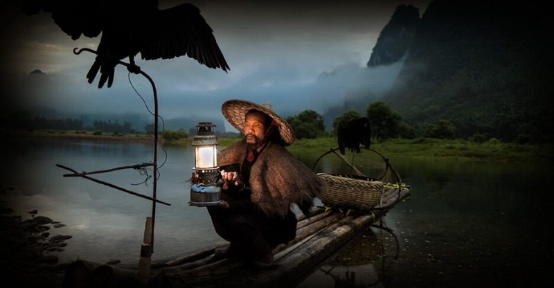 China Nomad Photo Tour Chinamen fishing on the water under the light of a lantern