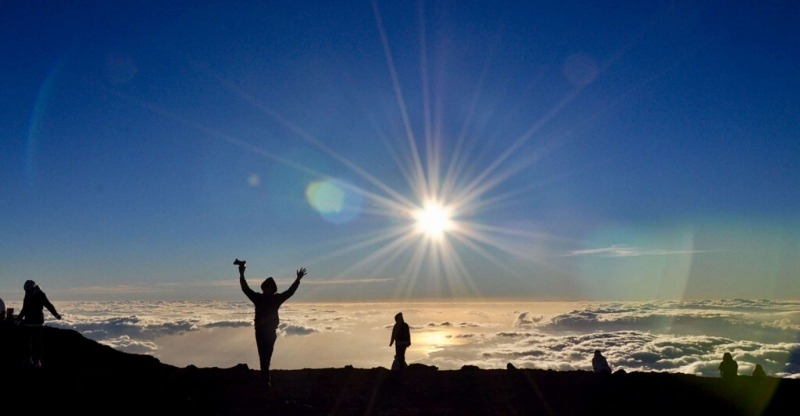 Silhouettes of people watching the sunrise at the peak of the Maui National Park