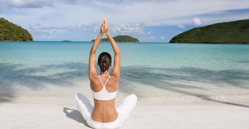 A female practicing yoga on the shoreline at the Sivananda Yoga Retreat