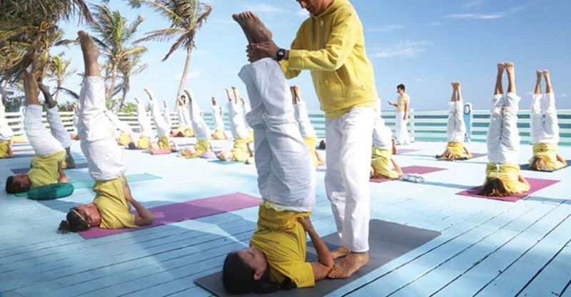 Group yoga practice overlooking the ocean at the Sivananda Yoga Resort