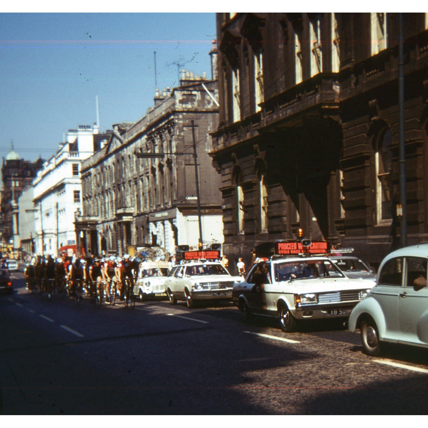 The riders and support vehicles head along George Street