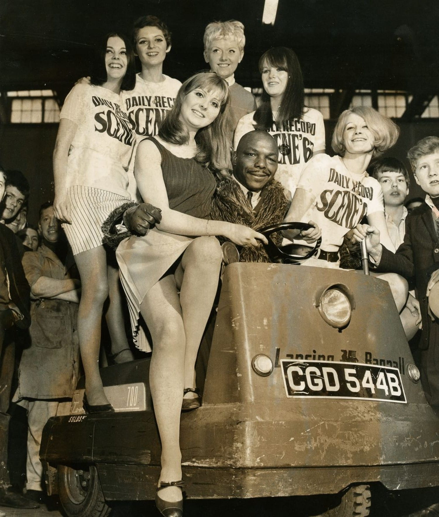 Former boxer turned band leader Freddie Mack with some of the Daily Record 'dollies'. Freddie, with his remarkable voice, later found fame as DJ Mr Superbad on Radio Clyde
