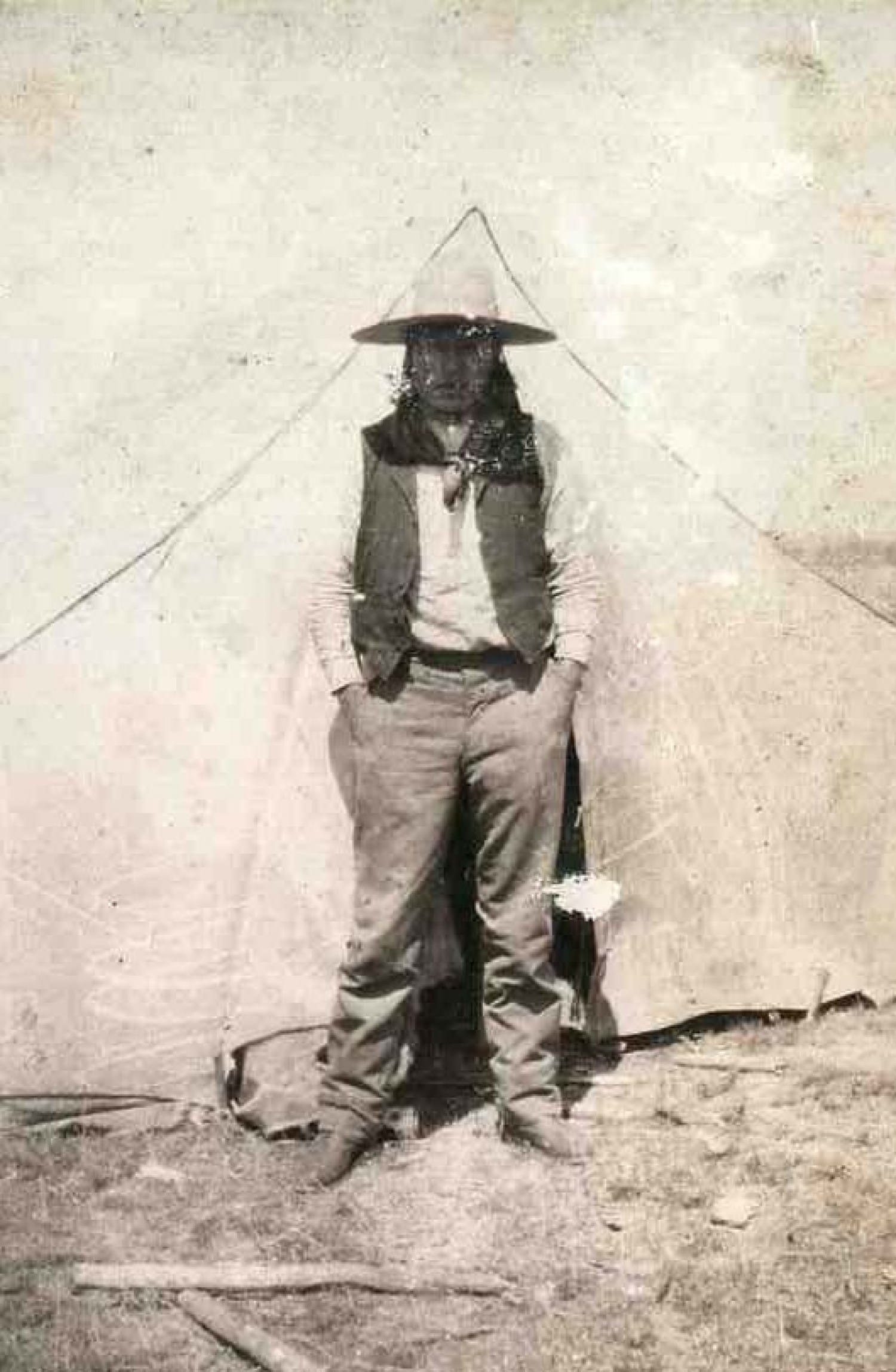 A Native American outside his tent