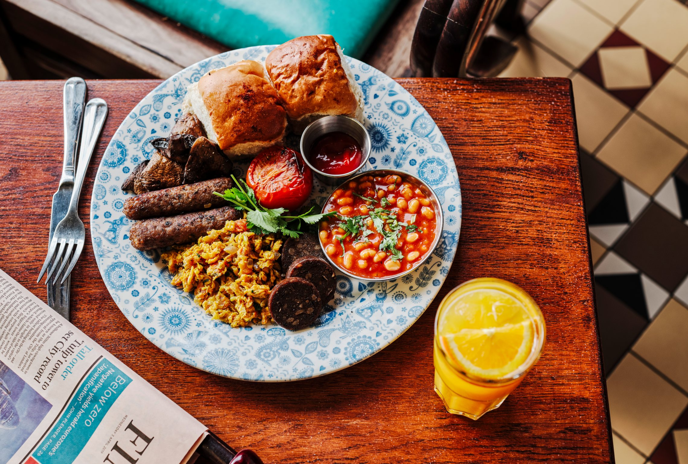 Dishoom's vegan Bombay breakfast next to a glass of orange juice and a Financial Times newspaper