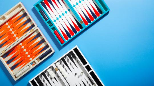 Three Jonathan Adler backgammon sets on a blue background