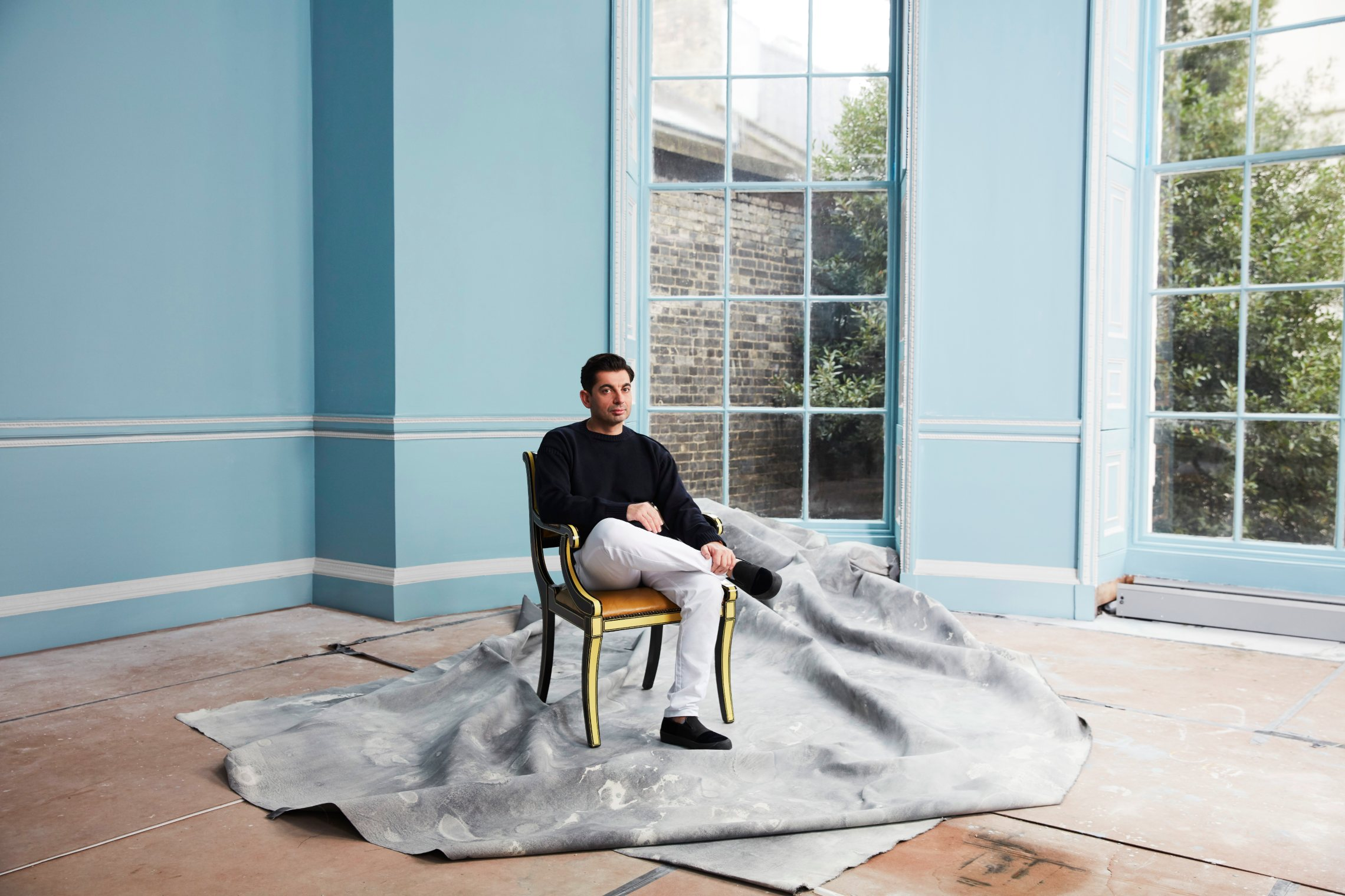 Francis Sultana sitting on a chair in a blue room with big windows