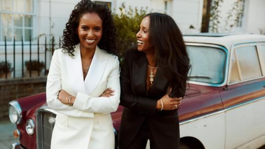 Two women standing in suits, leaning against a car and laughing