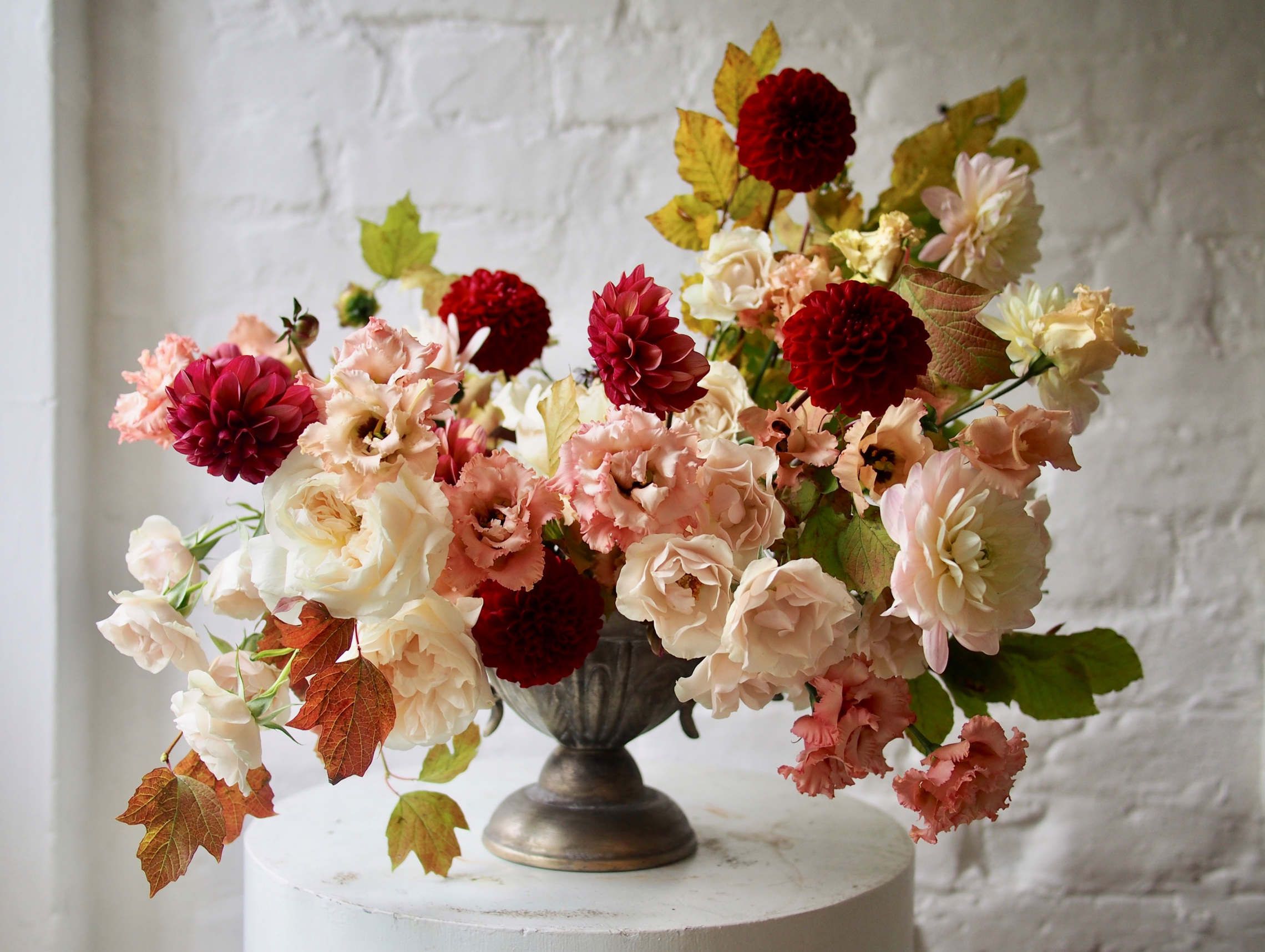 A bouquet of pink and red flowers in an antique urn by florist JamJar Flowers