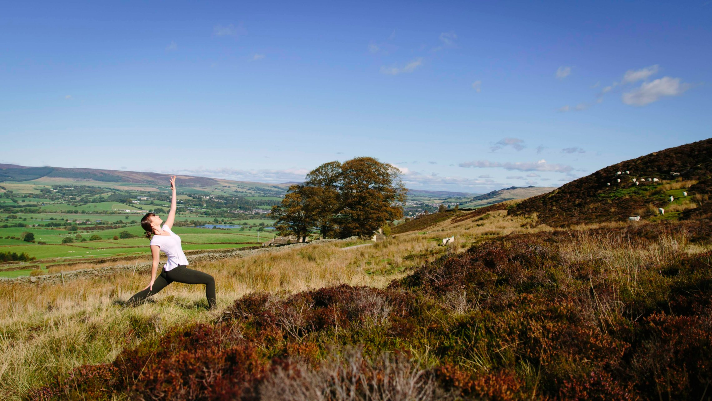 A woman in a white T-shirt and black leggings standing in a yoga pose on a hill, with Yorkshire countryside surrounding her