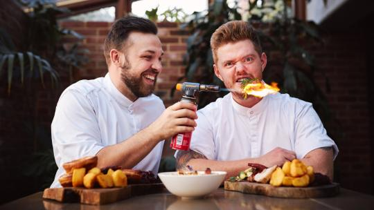 Scott Perkins and Jack Blumenthal wearing chef whites and playing with a blow torch, sitting in front of their Roasted box and roast dinners