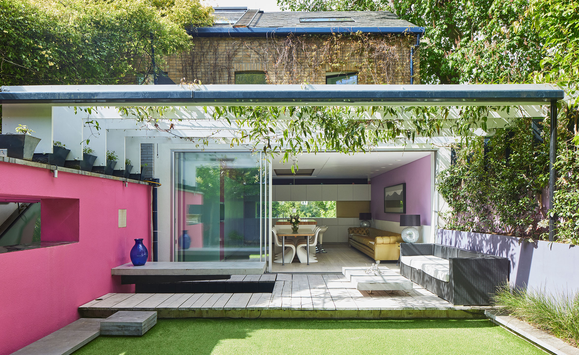 A garden with pink and lilac walls, looking through French doors to the dining room beyond