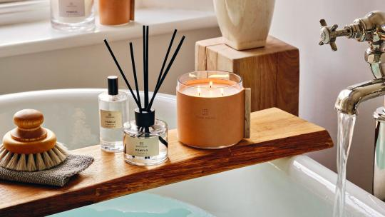 Soho Home candles, diffuser and room spray on a bath tray, perched on a bath with running water