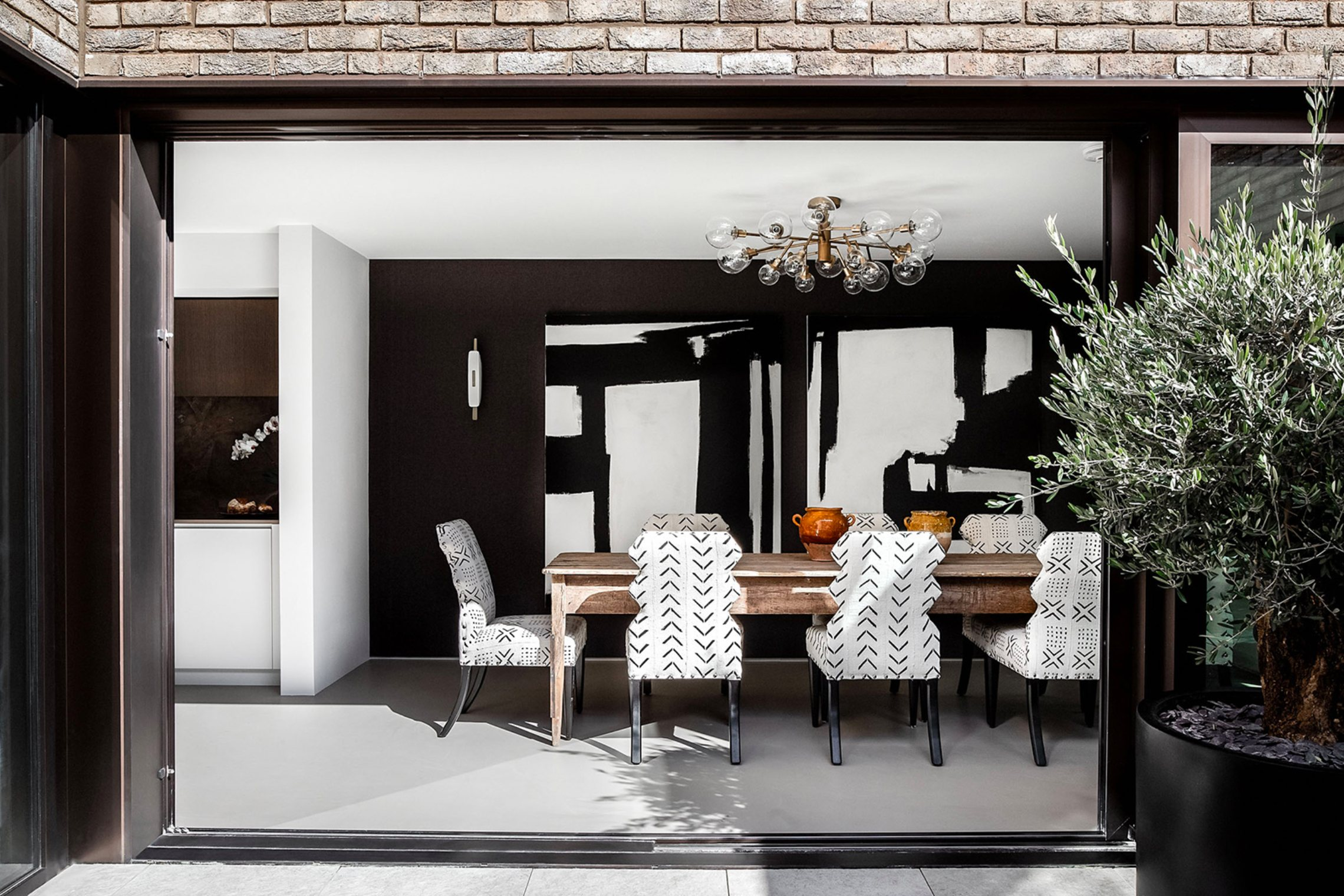 Looking through from the courtyard to the dining room, where a wooden dining table is surrounded by monochrome printed chairs