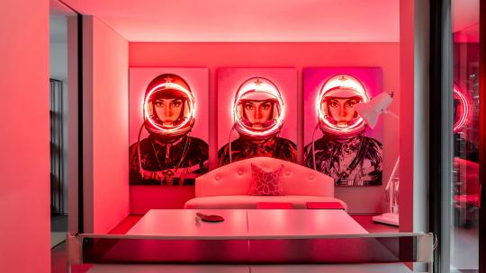 Three canvas prints of astronaughts with red LED lights around their helmets, hanging over a ping pong table