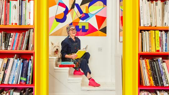 Morag Myerscough laughing while reading a book on the stairs, with her dog Elvis