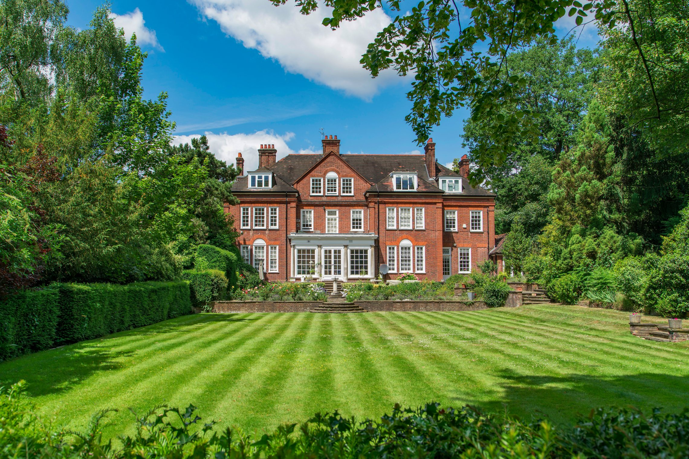 The exterior of a large red brick house and its gardens