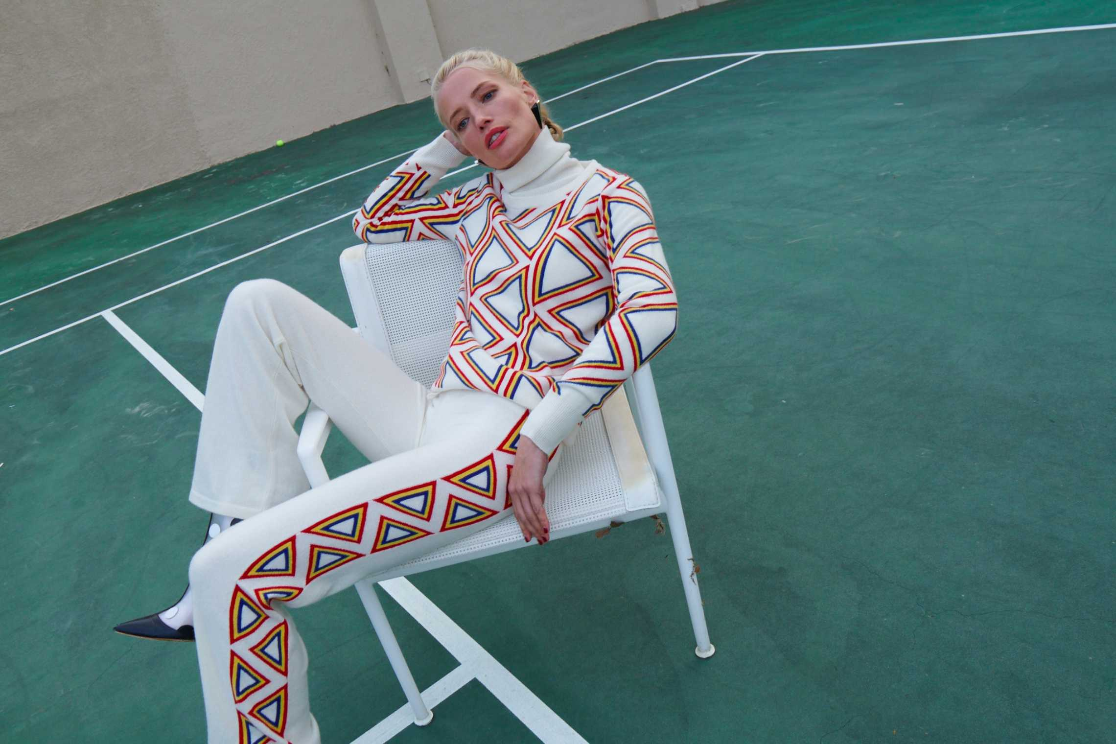 A woman wearing a white Madeleine Thompson tracksuit with rainbow stripes
