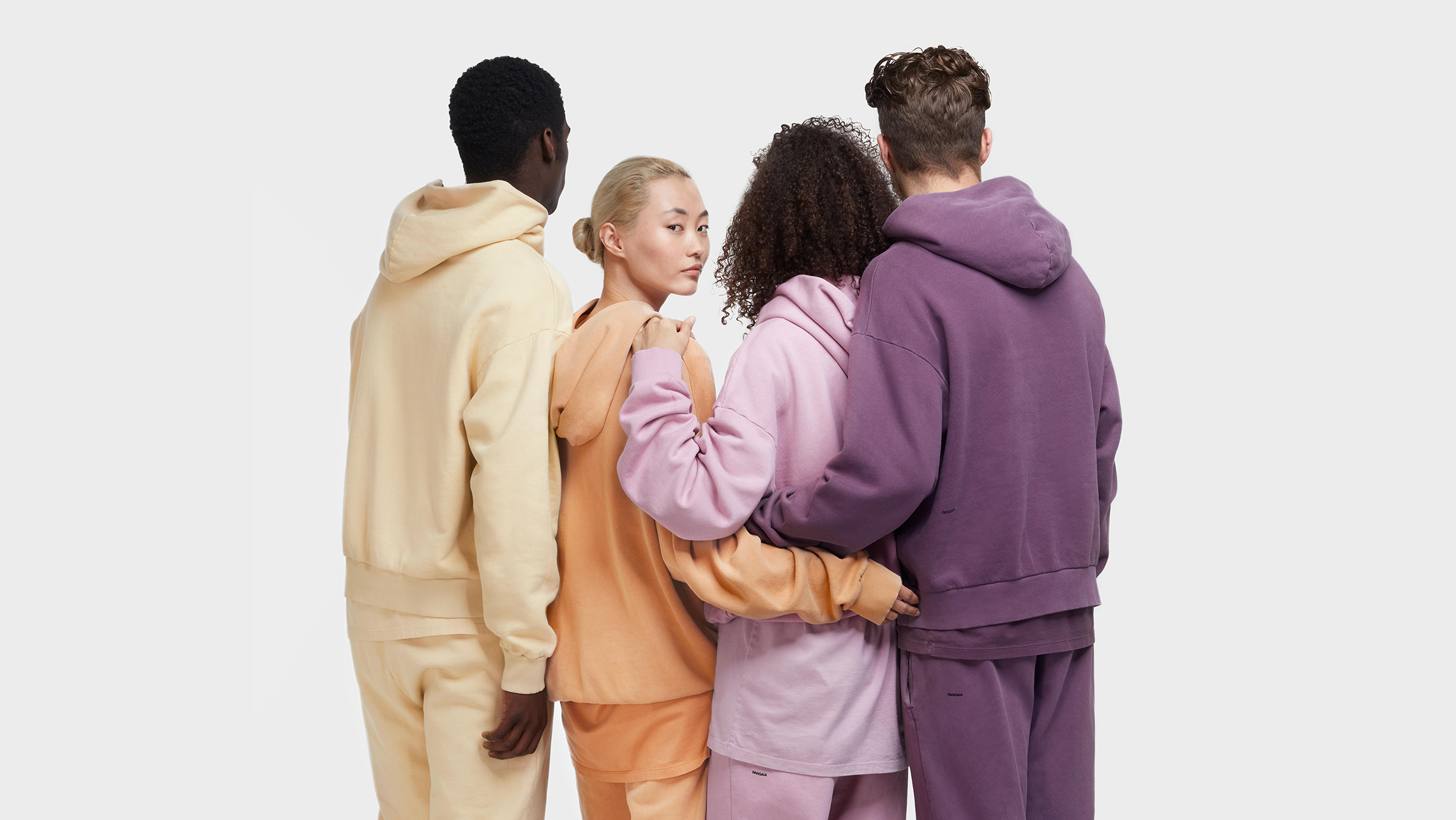 Four people wearing Pangaia tracksuits in pastel colours.