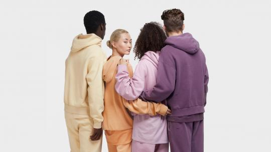 Four people wearing pastel-coloured Pangaia tracksuits, with their backs to the camera